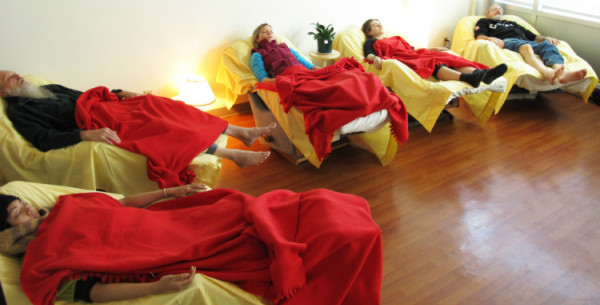 Five people sleeping during acupuncture treatment, covered in red blankets, lying in recliners arranged in a semi-circle.