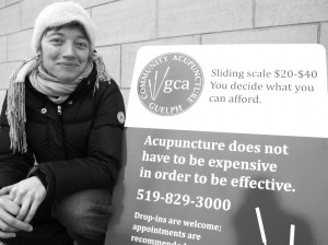 Lisa Baird from Guelph Community Acupuncture crouches beside her sandwich board