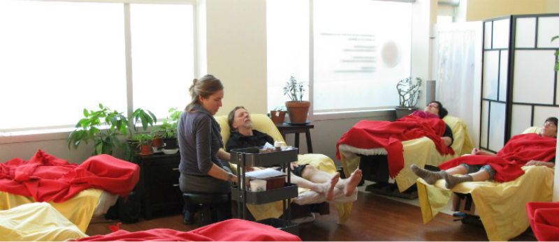 Community acupuncture practitioner sitting on a stool in the GCA group treatment room, in front of a bearded patient relaxing in a recliner, while several other patients sleep in recliners covered in red blankets in a loose circle in the room.