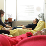 A woman sleeping under a red blanket in the foreground; in the background a practitioner treating a patient in a black shirt reclining on a lazyboy by two jade plants.