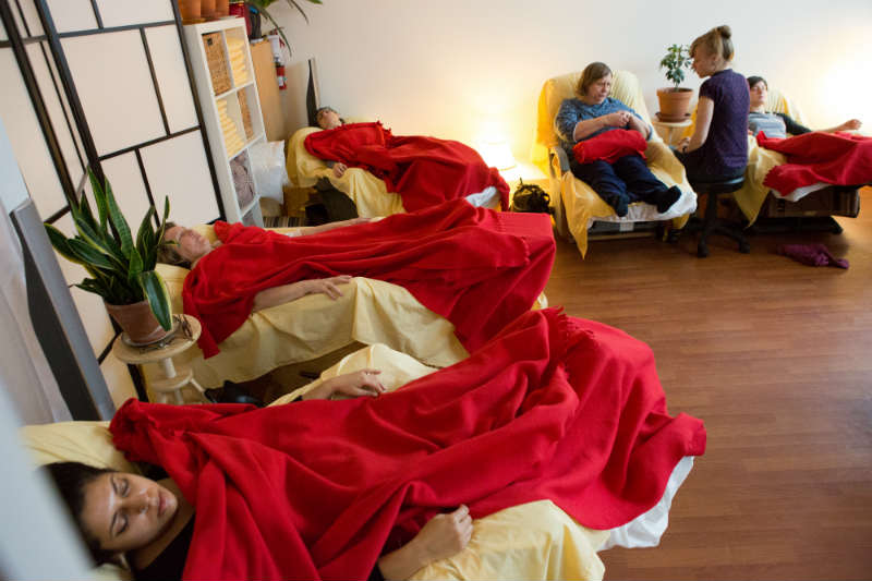 On one side, several people sleeping in recliners under red blankets. In the back of the room, a practitioner sitting on a stool facing a patient sitting upright in a recliner.