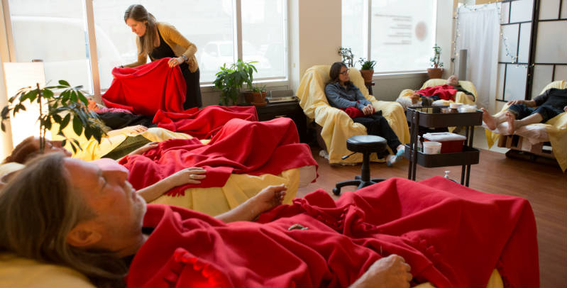 Treatment room full of patients seated or reclined under red blankets in lazyboys. Standing practitioner covering patient with red blanket.