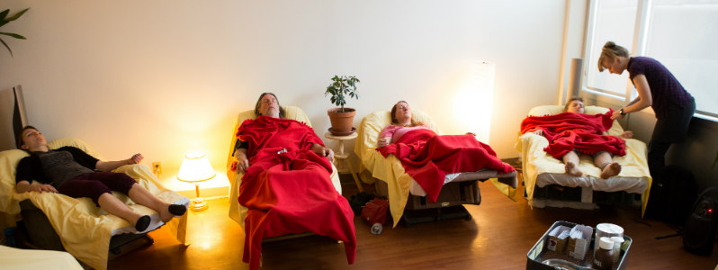 Four acupuncture patients reclining in a softly lit room, practitioner standing to the right tending to a patient.