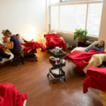 9 recliners in a semi-circle, each with a patient resting under red blankets. Practioner seated on a small black stool giving a treatment to one patient.