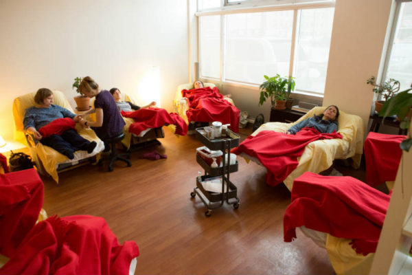 8 recliners in a semi-circle, each with a patient resting under red blankets. Practioner seated on a small black stool giving a treatment to one patient.