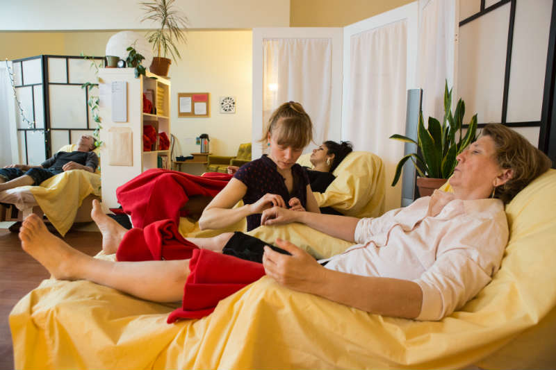 A practitioner sets a needle into a patient's wrist as the patient reclines in a lazyboy. Two other sleeping patients are visible in the background.