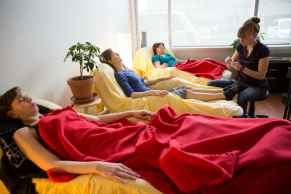 A row of three people reclining in lazyboys, covered with red blankets, with a practitioner seated on a stool glancing down at an acupuncture needle in her hand.