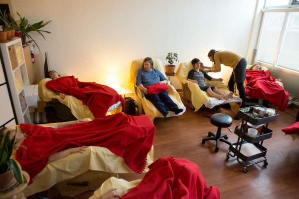 In a large room with natural lighting, a semi-circle of patients reclining in lazyboys, covered with red blankets. On the far right, a pracitioner bends over to set needles for a patient.