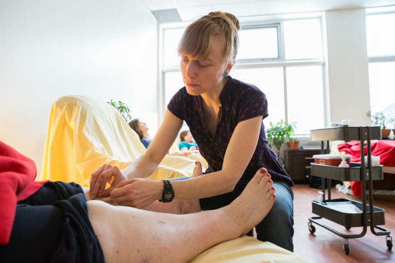 A practitioner setting needles into a patient's knee with a supply cart and three other sleeping patients in the background.
