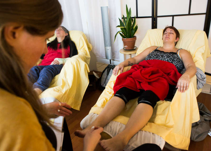 A practioner needling a patient's ankles; two patients visible in the background in recliners covered in yellow sheets.