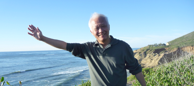 A balding man stands in the sunshine with a huge smile waves to the camera. Ocean and rugged coastline behind him.