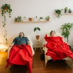 Four acupuncture patients sleeping under red blankets in four recliners lined up against a wall lined with plants.