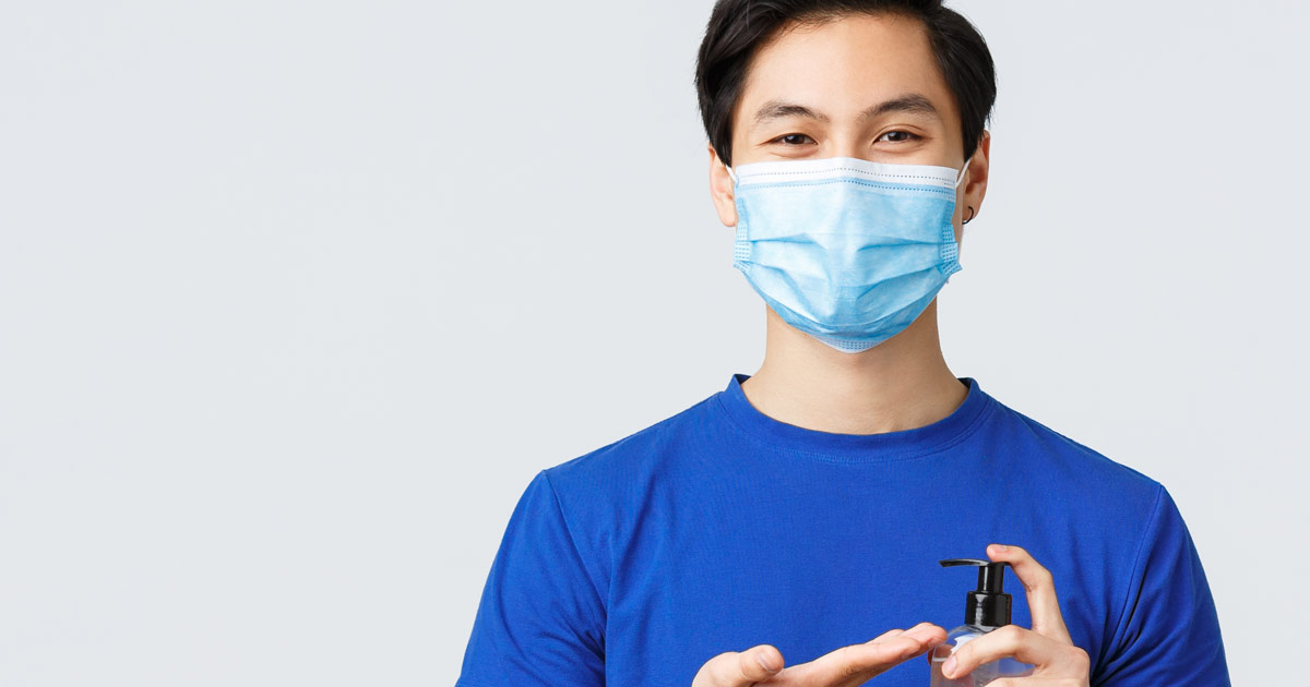 A person stands cleaning their hands and wearing a mask smiling.