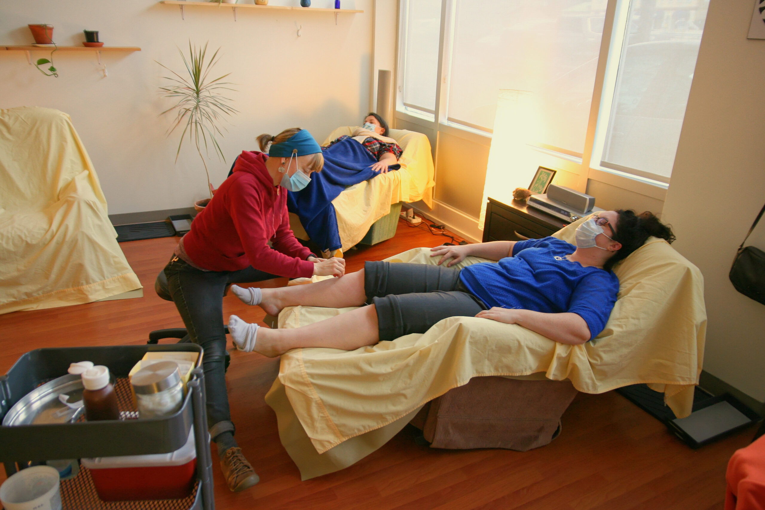A person in a surgical mask and red hoodie set acupuncture needles into someone's leg while they lie back in a recliner covered in a yellow sheet. In the background another masked patient leans back in a recliner covered in a yellow sheet under a blue blanket.