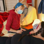 A person in a surgical mask and red hoodie and a person with long dark hair and cloth mask look at each other. The person with long dark hair leans back in a recliner covered with a yellow sheet.