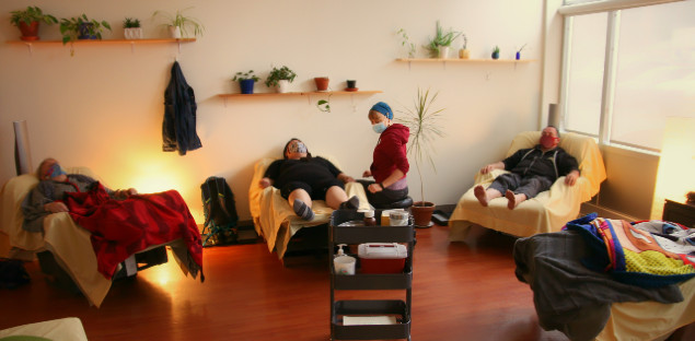 A wide shot of the treatment room. three masked patients leaning back with closed eyes in recliners covered in yellow sheets. To the right, someone's lower body covered in blankets is visible. A practitioner wearing a surgical mask and a red hoodie sits by of the patients, turning towards the camera. In the background, a large white wall with three wooden shelves, holding potted plants.